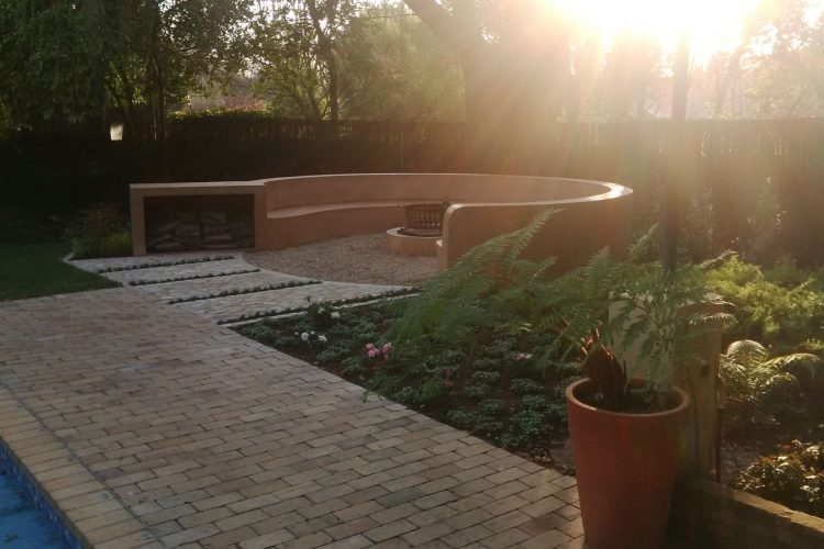 Firepit seating area in garden with steel floated cement finish